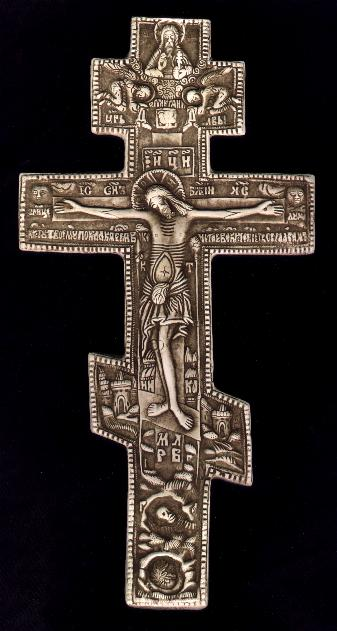 "Orthodox Cross - Based on an original Russian antique, c. 1780, which shows the crucified Christ, flanked by the sun and moon with the inscription in Slavonic, ""Jesus, O Master, I bow down to you."" Above Christ is a rooster (the rooster that crowed three times according to Christ's prophecy to Peter) and above that a depiction of God holding the world surmounted with a Byzantine cross with cherubim and seraphim on either side. There is a faint imprint of ""A"" and ""O"", Alpha and Omega as well.  On either side of Christ is the lance and the sponge associated with the Crucifixion, and a ""K"" and ""T"", meaning Kappa and Tau, beginning and end.  Below Christ is the city of Jerusalem, a thorn bush from which came the crown of thorns and a skull symbolizing Golgotha, the Place of Skulls, on which Jesus was crucified"